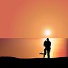 Liebevolle Paare auf Küste bei Sonnenuntergang