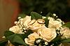 Золотые обручальные кольца лежат на букет роз | Фото